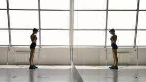 Het Kaukasische atletische brunette maakt haar sportkleding recht, kijkend in een spiegel stock video
