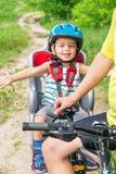 Het Kaukasische blije gelukkige kind heeft biking helm op de fiets Stock Foto