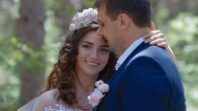 Het Kaukasische bruid en bruidegom stellen in het pijnboomhout stock footage
