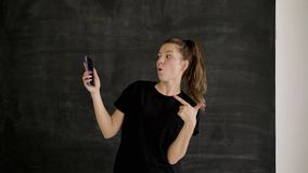 Het Kaukasische brunette in sportkleding houdt een smartphone in haar hand en toont klasse stock videobeelden