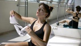 Het Kaukasische brunette in zwarte sportkleding koelt weg met witte handdoek op vloer stock footage