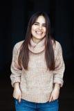 Het Kaukasische donkerbruine jonge mooie model van de meisjesvrouw met lang donker haar en bruine ogen in colsweater en jeans Stock Afbeeldingen