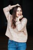 Het Kaukasische donkerbruine jonge mooie model van de meisjesvrouw met lang donker haar en bruine ogen in colsweater en jeans stock afbeelding