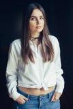 Het Kaukasische donkerbruine jonge mooie model van de meisjesvrouw met lang donker haar en de bruine ogen in wit overhemd bonden  Royalty-vrije Stock Foto's
