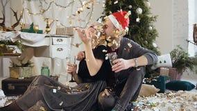 Het Kaukasische jonge paar viert Kerstmis of Nieuwjaar samen, zij zitting op de vloer, dichtbij drinkend wijn van stock footage