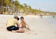 Het Kaukasische jongen en vader spelen met zand bij tropisch strand stock foto's