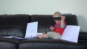 Het Kaukasische kind knoeit thuis met de documenten van vaderdocumenten op bank stock videobeelden