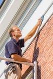 Het Kaukasische mannelijke schilder het schoonmaken dak vormen met doek royalty-vrije stock foto