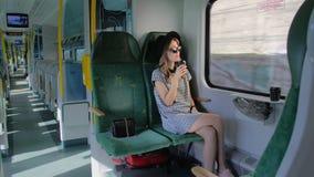 Het Kaukasische meisje in een hoed reist door trein Het drinken van koffie van een document kop Zij is één De trein gaat de tunne stock footage