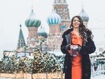 het Kaukasische meisje in een rode kleding zonder kokers speelt op een harmonika in de winter een blizzard tegen de achtergrond v royalty-vrije stock afbeeldingen
