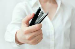 Het Kaukasische meisje in een wit overhemd houdt in haar hand een zwarte nietmachine voor document royalty-vrije stock afbeeldingen