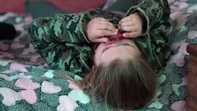Het Kaukasische meisje liggen op de laag doet de truc met de vingerspinner 4K stock footage