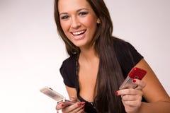 Het Kaukasische meisje van Nice met twee mobiele telefoons Stock Afbeeldingen