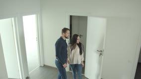 Het Kaukasische paar beklimt de treden houdend handen en bekijkt rond een nieuwe flat die gelukkig zijn stock video