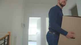 Het Kaukasische paar brengt kartondoos in een nieuw huis en het kijken rond gelukkig en opgewekt het zijn stock videobeelden