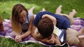 Het Kaukasische paar heeft een goede tijdoudoors met hun zoon Het liggen op een plaid in het park Picknick Vaderspelen met stock footage