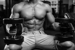 Het Kaukasische sexy geschiktheids mannelijke model voert oefening met domoor uit Stock Foto