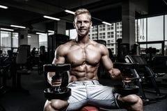Het Kaukasische sexy geschiktheids mannelijke model voert oefening met domoor uit Stock Afbeelding