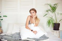 Het Kaukasische slaperige jonge aantrekkelijke vrouw voelen slaperig na ontwaakte, zit op het bed die slechte stemming na slapelo stock foto's