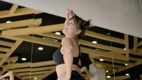 Het Kaukasische sportieve brunette stelt voor de camera Op de achtergrond is een spiegel stock video