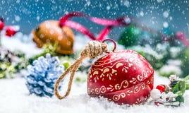 Het kenwijsjeklokken van Kerstmisballen Rood lint met tekst Gelukkige Kerstmis Sneeuw abstracte achtergrond en decoratie Stock Afbeeldingen