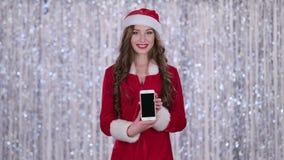 Het kerstmanmeisje houdt de telefoon in haar handen en onderzoekt de afstand De achtergrond van Bokeh stock videobeelden