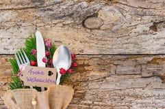 Het Kerstmisbestek op rustiek hout met etiket en Duitse teksten, Frohe Weihnachten, betekent Vrolijke Kerstmis stock afbeelding