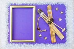 Het Kerstmiskader bestaat uit witte versieringen: sneeuwvlokken, rendier, ski en giftdozen op blauwe achtergrond E stock fotografie