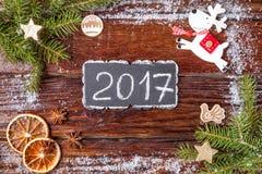 Het Kerstmiskader van spar wordt vertakt zich, stuk speelgoed herten, sneeuw en sinaasappelen, op houten oude bruine achtergrond  Stock Foto