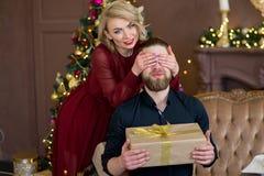 Het Kerstmispaar, gelukkige jonge vrouwelijke verrassingsmens behandelt zijn ogen Royalty-vrije Stock Fotografie