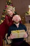 Het Kerstmispaar, gelukkige jonge vrouwelijke verrassingsmens behandelt zijn ogen Stock Foto's