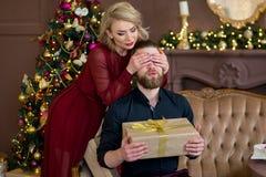 Het Kerstmispaar, gelukkige jonge vrouwelijke verrassingsmens behandelt zijn ogen Stock Fotografie