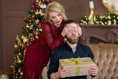 Het Kerstmispaar, gelukkige jonge vrouwelijke verrassingsmens behandelt zijn ogen royalty-vrije stock foto's