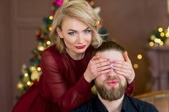 Het Kerstmispaar, gelukkige jonge vrouwelijke verrassingsmens behandelt zijn ogen Royalty-vrije Stock Afbeeldingen