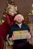 Het Kerstmispaar, gelukkige jonge vrouwelijke verrassingsmens behandelt zijn ogen Stock Foto