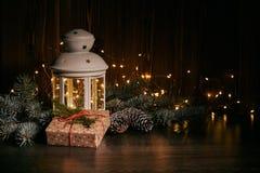 Het Kerstmisstilleven met spar vertakt zich, giftdoos, decoratie en lamp op een donkere houten achtergrond met LEIDENE lichte sli stock foto's