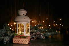 Het Kerstmisstilleven met spar vertakt zich, giftdoos, decoratie en lamp op een donkere houten achtergrond met LEIDENE lichte sli royalty-vrije stock foto
