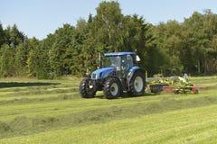 Het kidding van geschud gras met blauwe tractor met Royalty-vrije Stock Afbeeldingen