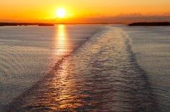 Het kielzog van het schip bij zonsondergang Stock Foto