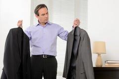 Het kiezen van een kostuum voor vergadering. Rijpe zakenman die zich met a bevinden Stock Afbeelding