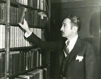 Het kiezen van een te lezen bibliotheekboek Royalty-vrije Stock Afbeeldingen