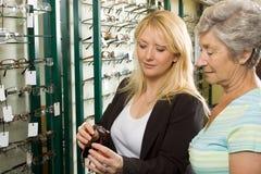 Het kiezen van glazen bij de opticien Stock Foto