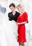 Het kiezen van huwelijkskleding bij de bruids salon Stock Afbeeldingen