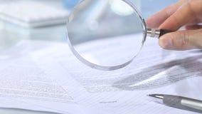 Het kijken door een vergrootglas aan contract en handhandtekening