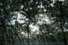 Het kijken door venster met de daling van het regenwater en vage aardachtergrond Stock Fotografie