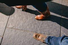Het kijken neer tegen twee paren voeten die op zwarte stad lopen pav Stock Afbeeldingen