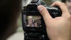 Het kijken op camcordervertoning tijdens het schieten van vrouwen stock videobeelden