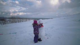 Het kind beeldhouwt sneeuwman op heuvel op achtergrond van stad stock video