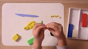 Het kind beeldhouwt van kleihanden van de ambachten en naleplyaet het op de raad, close-up stock video