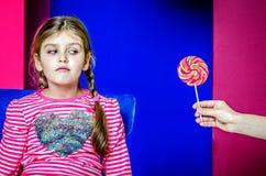 Het kind bekijkt incredulously het suikergoed Royalty-vrije Stock Foto